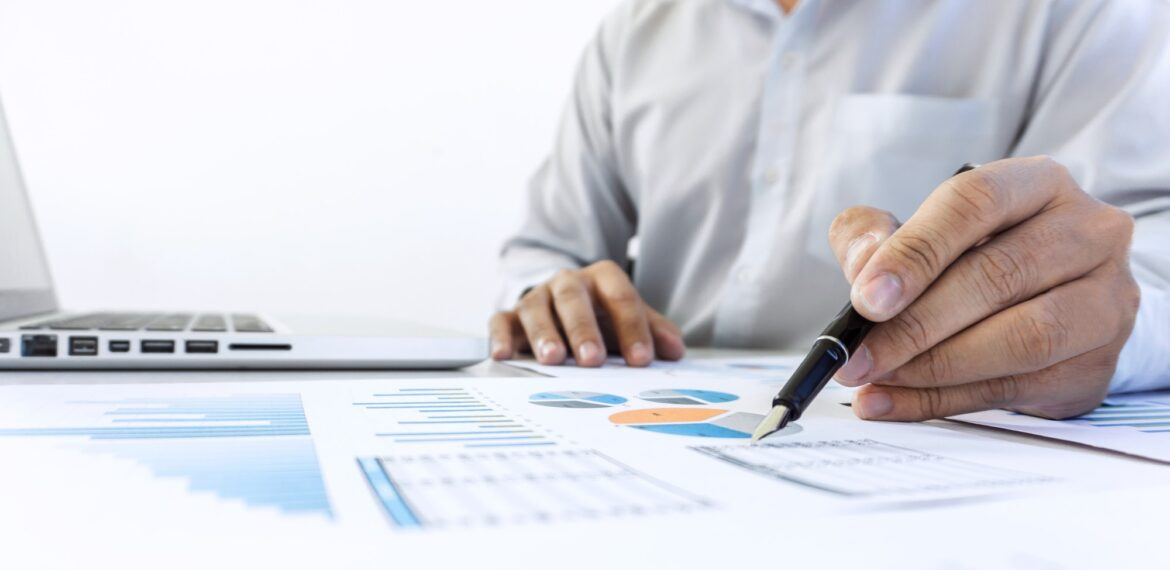 Businessman accountant working audit and calculating expense financial data on graph documents