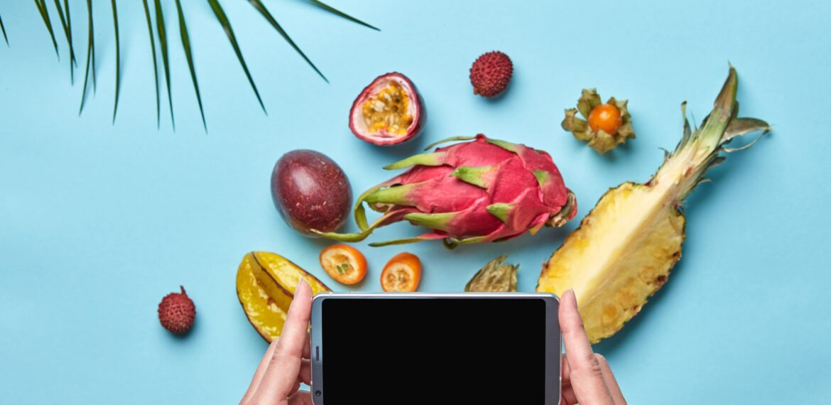 In the women's hand is mobile, many different exotic fruits on a blue background decorated with